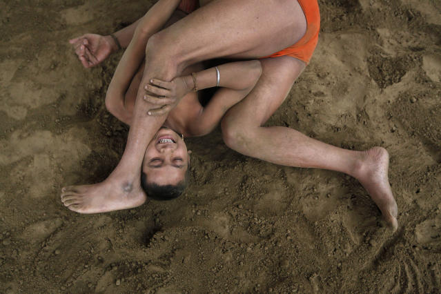 "Wrestlers fight at a permanent mud wrestling ring at ""Sia Ram bhajan samati akhaara"", a traditional Indian wrestling training centre, on the banks of the river Ganges in Kolkata February 17, 2013. India's government will seek the support of other countries where wrestling is popular to help the sport remain an Olympic discipline, the country's sports minister said on Wednesday. Wrestlers fought friendly matches at the training centre on Sunday to support the movement to reinstate wrestling as an Olympic sport, a senior wrestler and trainer said. REUTERS/Rupak De Chowdhuri (INDIA - Tags: SPORT OLYMPICS WRESTLING TPX IMAGES OF THE DAY) - RTR3DWIT"