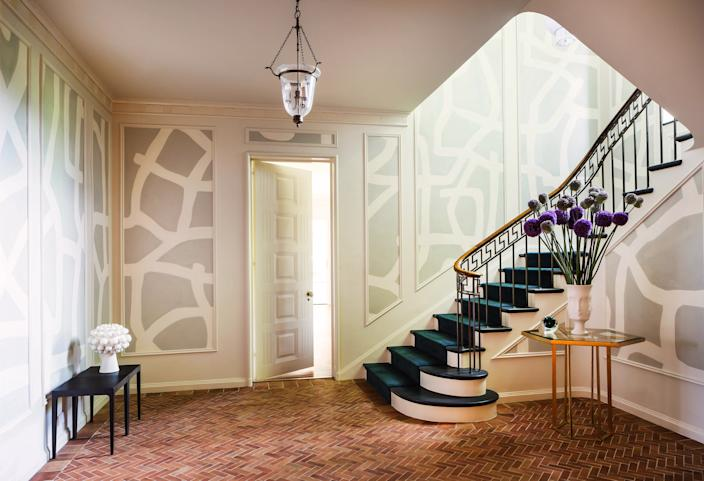 "<div class=""caption""> The foyer is the most dramatic transformation in the home. Previously, it had all been done in shades of brown. The designer brightened up the space by first painting the walls <a href=""https://www.benjaminmoore.com/en-us"" rel=""nofollow noopener"" target=""_blank"" data-ylk=""slk:Benjamin Moore"" class=""link rapid-noclick-resp"">Benjamin Moore</a>'s Feather Down—a cool white hue—and then placed a gray-and-white-patterned wallpaper made of Japanese tea paper by <a href=""https://porterteleo.com/"" rel=""nofollow noopener"" target=""_blank"" data-ylk=""slk:Porter Teleo"" class=""link rapid-noclick-resp"">Porter Teleo</a> in the molding panels. The entryway table is from <a href=""https://www.interludehome.com/"" rel=""nofollow noopener"" target=""_blank"" data-ylk=""slk:Interlude Home"" class=""link rapid-noclick-resp"">Interlude Home</a> and the low table is a one-of-a-kind piece from <a href=""https://www.stephanehubert.com/"" rel=""nofollow noopener"" target=""_blank"" data-ylk=""slk:Stephane Hubert Design"" class=""link rapid-noclick-resp"">Stephane Hubert Design</a>. </div>"