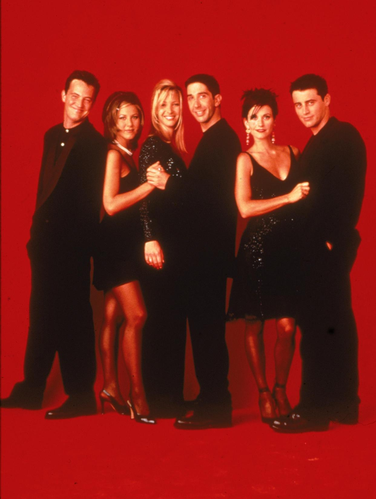 Promotional portait of the cast of the television series, 'Friends,' wearing black against a red backdrop, circa 1995. L-R: Matthew Perry, Jennifer Aniston, Lisa Kudrow, David Schwimmer, Courteney Cox, and Matt LeBlanc. (Photo by Warner Brothers Television/Fotos International/Courtesy of Getty Images)