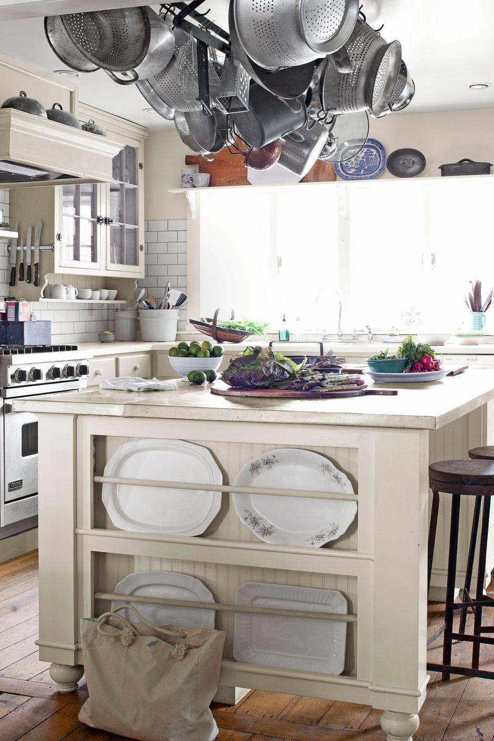 """<p>The kitchen island in this <a href=""""https://www.countryliving.com/home-design/house-tours/g1263/farmhouse-decorating-ideas/"""" rel=""""nofollow noopener"""" target=""""_blank"""" data-ylk=""""slk:Ohio farmhouse"""" class=""""link rapid-noclick-resp"""">Ohio farmhouse</a> boasts a custom zinc top crafted by a local metal shop and built-in racks for displaying prized serving pieces. Classic white subway tile forms the backsplash. </p>"""