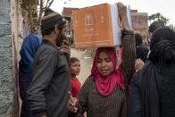 A woman carries a carton filled with food distributed by the non-governmental organization Resala Nour Ala Nour to people who have been highly affected by the coronavirus outbreak, in Cairo, Egypt, Thursday, April 9, 2020. (AP Photo/Nariman El-Mofty)