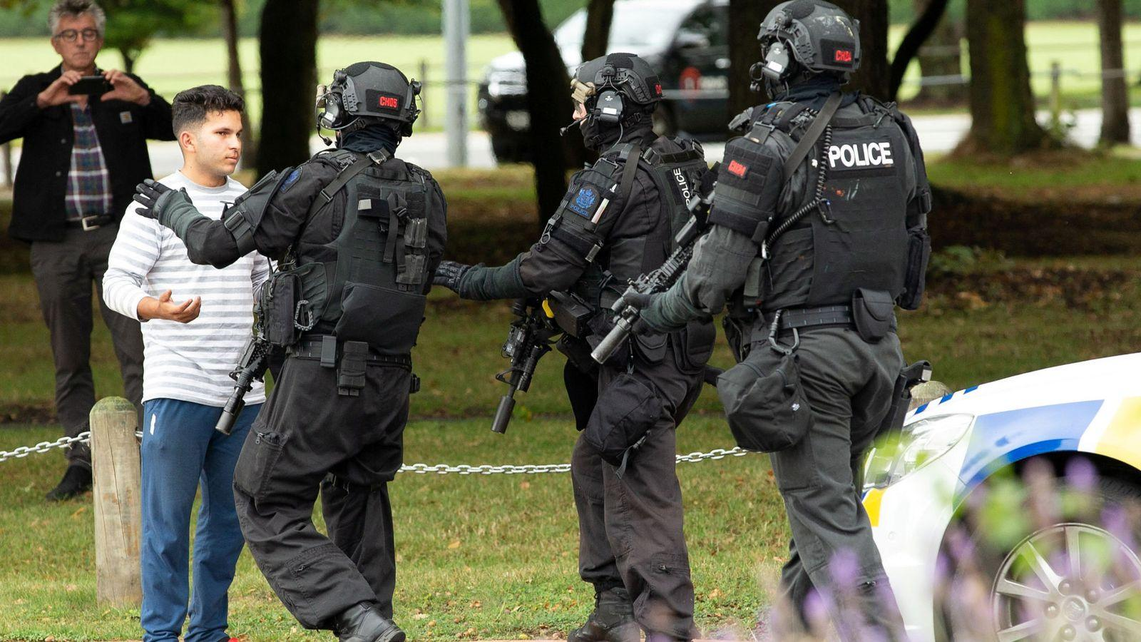 Armed officers push back members of the public from the scene