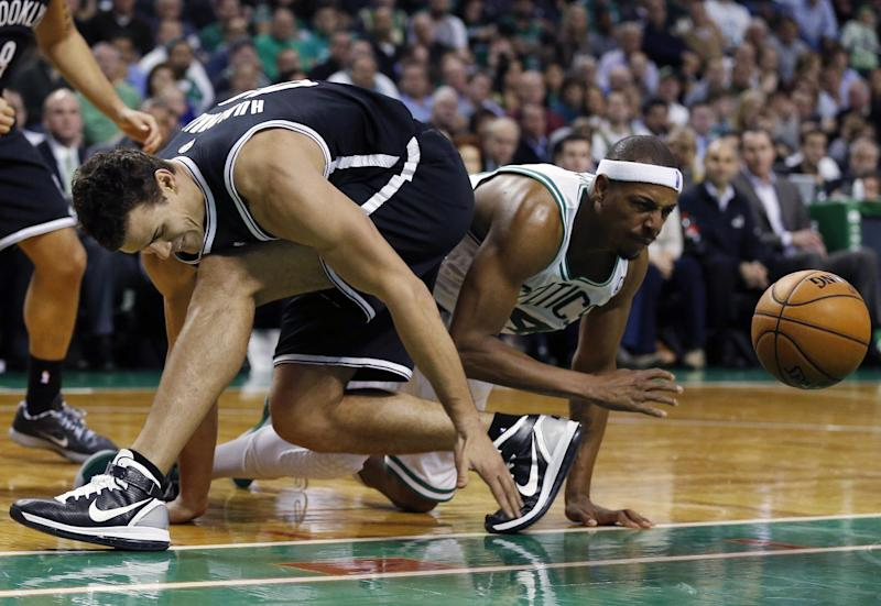 Brooklyn Nets' Kris Humphries, left, and Boston Celtics' Paul Pierce scramble for a loose ball in the second quarter of an NBA basketball game in Boston, Wednesday, Nov. 28, 2012. (AP Photo/Michael Dwyer)