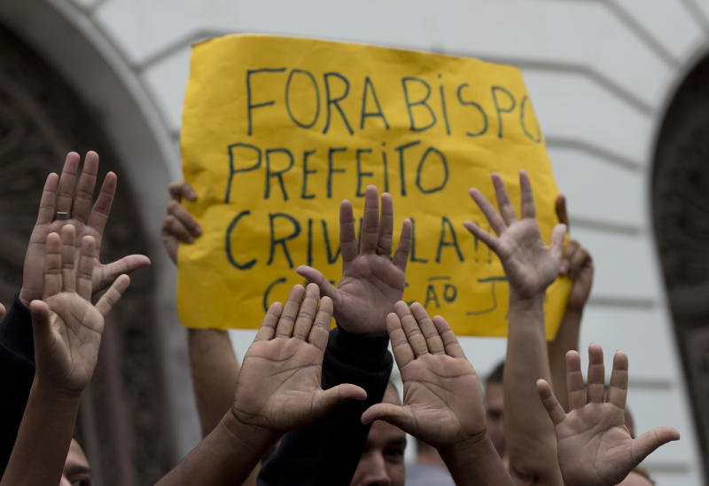 """Supporters of Rio Mayor Marcelo Crivella raise their hands in front of a sign that reads in Portuguese: """"Out Bishop, Mayor Crivella, Impeachment now"""" during a protest in front City Hall in Rio de Janeiro, Brazil, Thursday, July 12, 2018. Rio's city council is analyzing two impeachment processes against Crivella who is accused of using his position to benefit members of the Evangelical church. (AP Photo/Silvia Izquierdo)"""