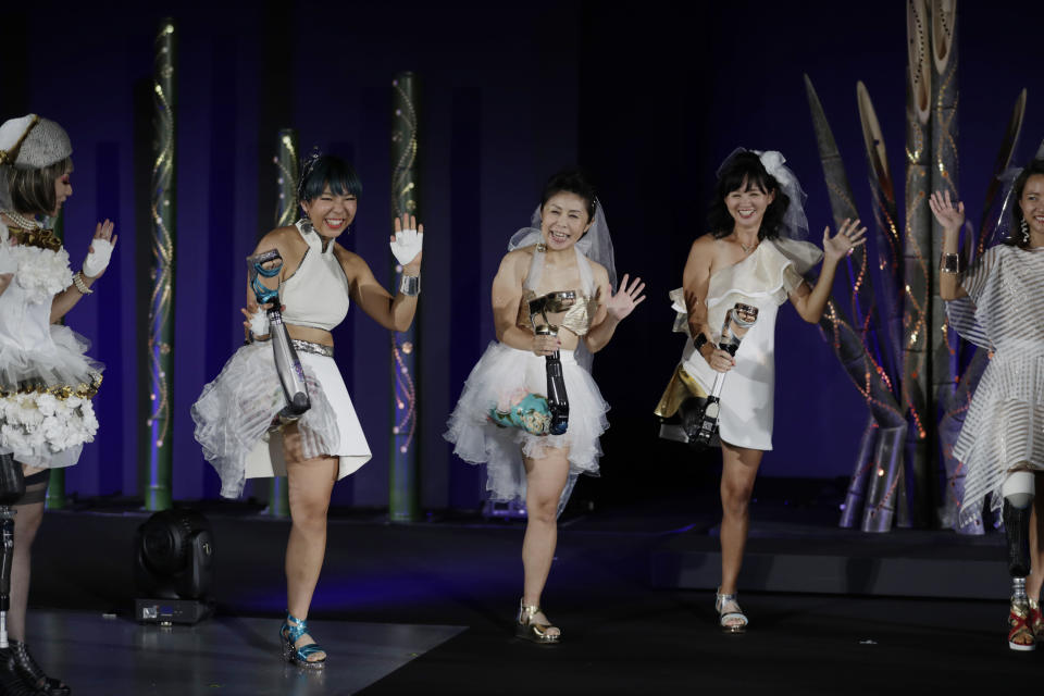 "Kaede Maegawa, a Paralympian, from second left, Hitomi Onishi, a Paralympian, and Sayaka Murakami, an athlete, pose for a photo at the end of a fashion show dubbed ""Amputee Venus Show"" they participated in Tokyo on Tuesday, Aug. 25, 2020. The fashion show was held in conjunction with the opening of the Tokyo Paralympic Games, now scheduled to open on Aug. 24, 2021. (AP Photo/Hiro Komae)"