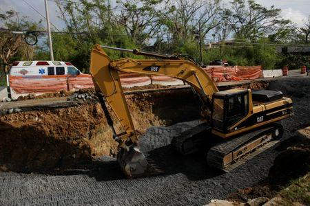 A crane is seen inside a sinkhole caused by Hurricane Maria at a construction site along Puerto Rico Highway 2, outside San Juan, Puerto Rico, October 12, 2017.   REUTERS/Shannon Stapleton