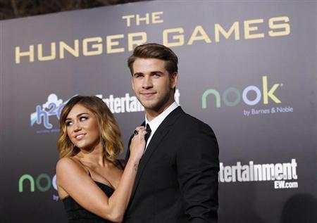 "Cast member Liam Hemsworth poses with actress Miley Cyrus at the premiere of ""The Hunger Games"" at Nokia theatre in Los Angeles, California March 12, 2012 in this file picture. REUTERS/Mario Anzuoni"