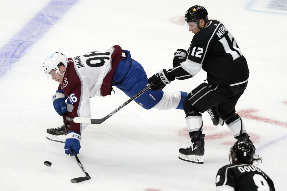 Colorado Avalanche right wing Mikko Rantanen, left, reaches for the puck in front of Los Angeles Kings center Trevor Moore (12) during the second period of an NHL hockey game Friday, May 7, 2021, in Los Angeles. (AP Photo/Marcio Jose Sanchez)