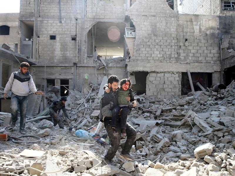 A man carries an injured boy as he walks on rubble of damaged buildings in the rebel held besieged town of Hamouriyeh, eastern Ghouta: Reuters