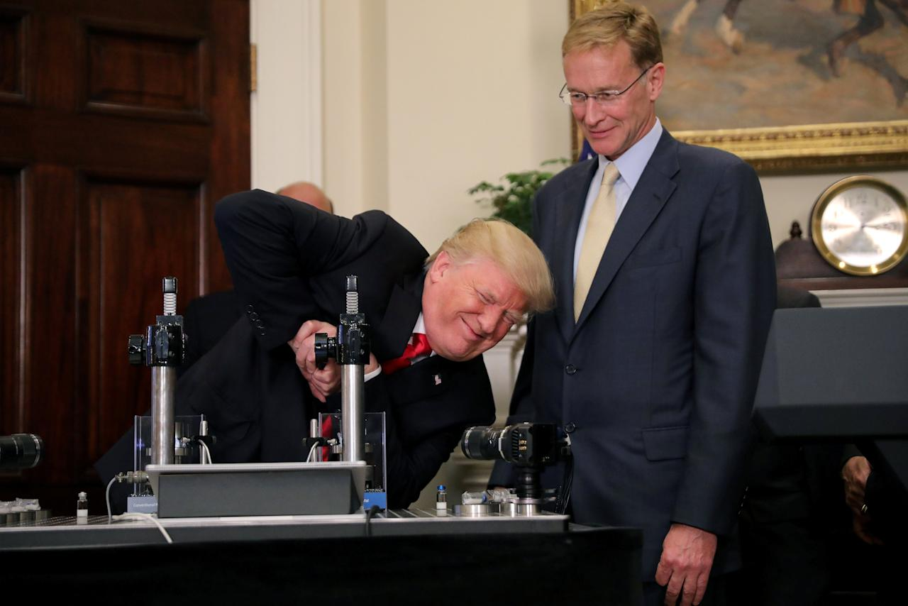 "U.S. President Donald Trump participates in a strength vial test accompanied by Corning Pharmaceutical Glass Chairman and CEO Wendell Weeks during a ""Made in America"" event on pharmaceutical glass manufacturing, at the Roosevelt Room of the White House in Washington, U.S., July 20, 2017. REUTERS/Carlos Barria     TPX IMAGES OF THE DAY"