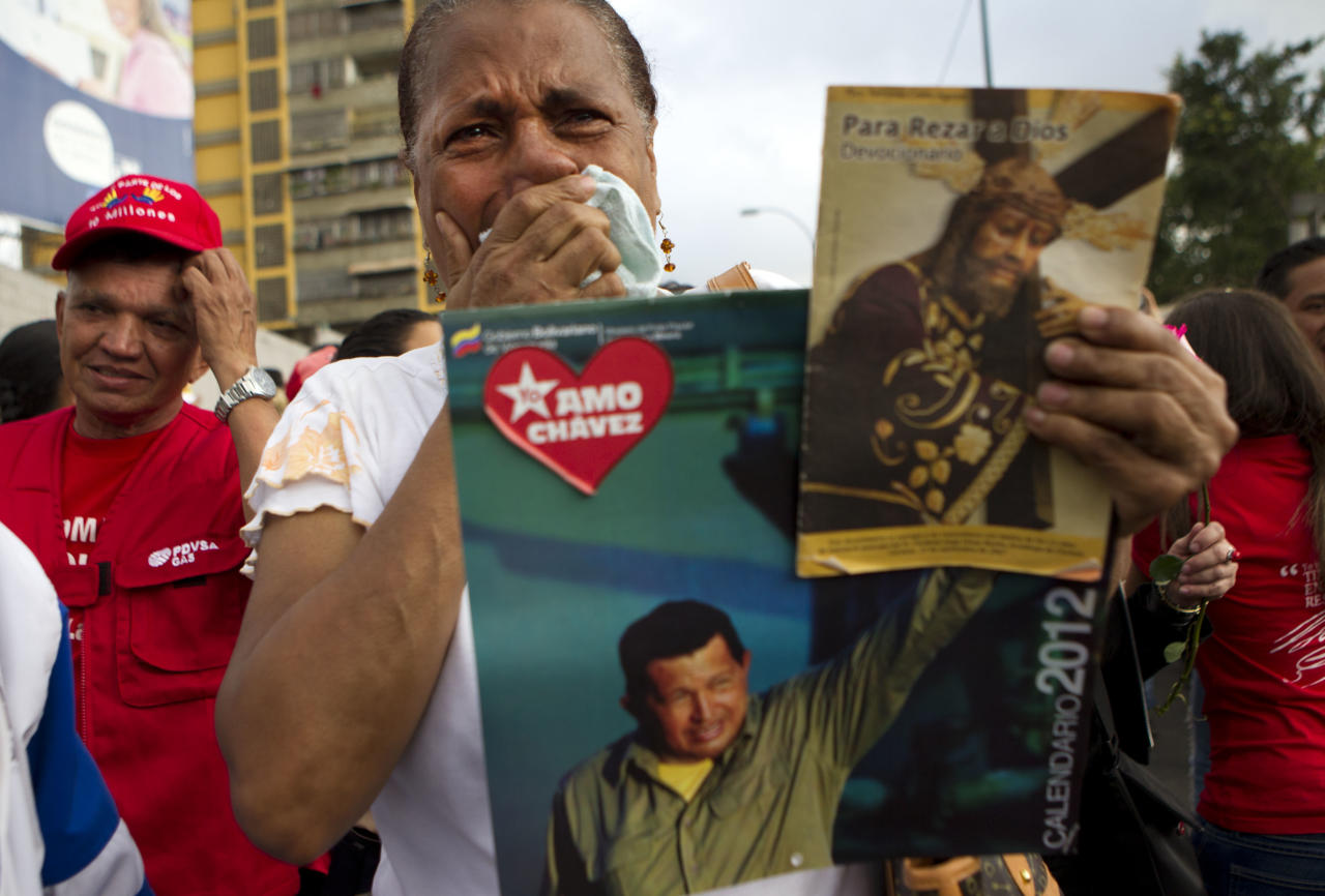 "A supporter of Venezuela's President Hugo Chavez cries as she holds a picture of him, as well as a poster of Jesus, during his caravan to the airport in Caracas, Venezuela, Friday Feb. 24, 2012. Chavez bid an emotional goodbye to soldiers and supporters and waved to crowded streets in Caracas on his way to Cuba for urgent surgery to remove a tumor he says is probably malignant. the poster reads in Spanish ""I love Chavez."" (AP Photo/Ariana Cubillos)"