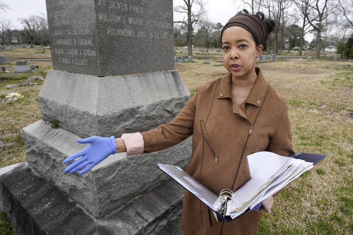 Nadia Orton, a genealogist and family historian in Virginia, holds a binder of research next to a monument to black Civil War Union soldiers at the Lincoln Memorial Cemetery in Portsmouth, Va., Tuesday, March 23, 2021. Orton has worked tracing her own family and others to historically Black cemeteries. (AP Photo/Steve Helber)