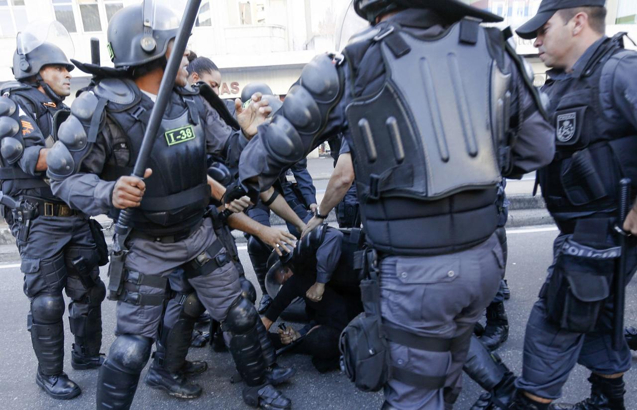 A demonstrator (C, rear) is detained by riot police before the 2014 World Cup final match between Argentina and Germany in Rio de Janeiro, July 13, 2014. REUTERS/Marco Bello (BRAZIL - Tags: POLITICS SOCCER CRIME LAW SPORT CIVIL UNREST WORLD CUP)