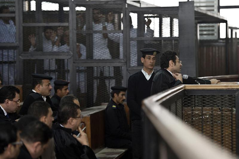 Egyptian lawyer Khaled Abou Bakr (R) talks to the judge during the trial of Al-Jazeera's journalists standing inside the defendants cage as they are charged with supporting the Muslim Brotherhood on March 5, 2014 at Cairo's Tora prison