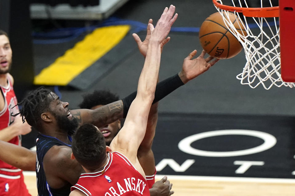 Orlando Magic forward James Ennis III, left, drives to the basket against Chicago Bulls forward Thaddeus Young, back, and guard Tomas Satoransky during the first half of an NBA basketball game in Chicago, Wednesday, April 14, 2021. (AP Photo/Nam Y. Huh)