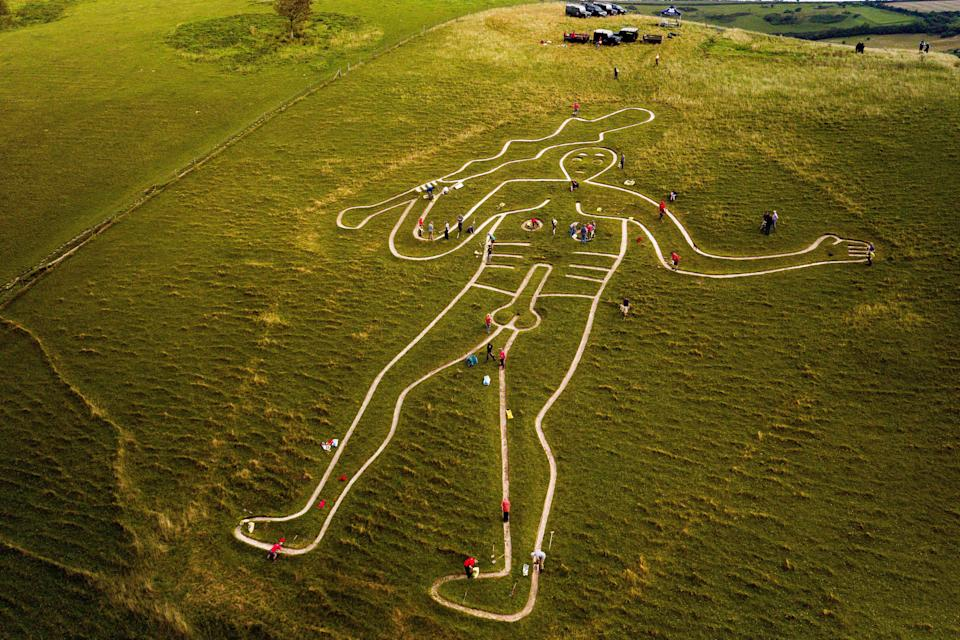 Volunteers work to repair and refresh the ancient Cerne Abbas Giant in Dorset, England. (Photo: Ben Birchall - PA Images via Getty Images)