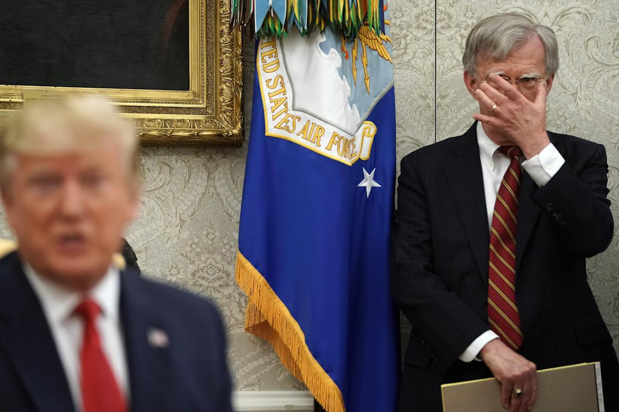 White House national security adviser John Bolton, right, listens to President Donald Trump in the Oval Office at the White House on July 18, 2019.