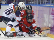 Lauriane Rougeau (5) and Marie-Philip Poulin of Canada (29) fight for the puck against Lyndsey Fry of the United States (18) during the second period of the women's gold medal ice hockey game at the 2014 Winter Olympics, Thursday, Feb. 20, 2014, in Sochi, Russia. (AP Photo/Matt Slocum)