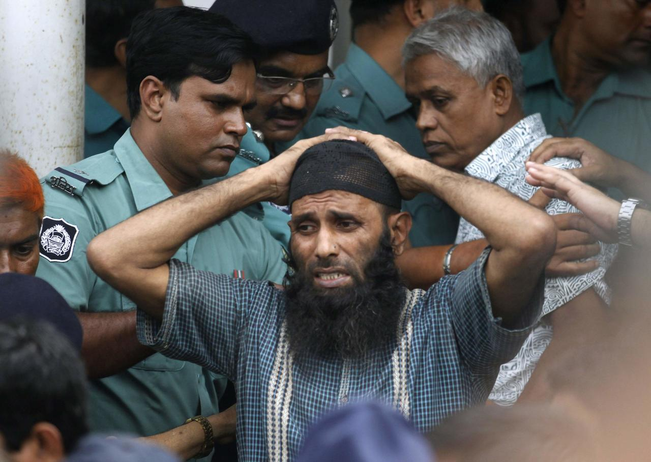 A prisoner reacts as police force him into a van after the verdict for a 2009 mutiny is announced, in Dhaka November 5, 2013. A special court in Bangladesh on Tuesday sentenced to death more than 150 people, from among hundreds of mutineers accused of murder and arson at the headquarters of the country's border guards in 2009. REUTERS/Andrew Biraj (BANGLADESH - Tags: CRIME LAW)