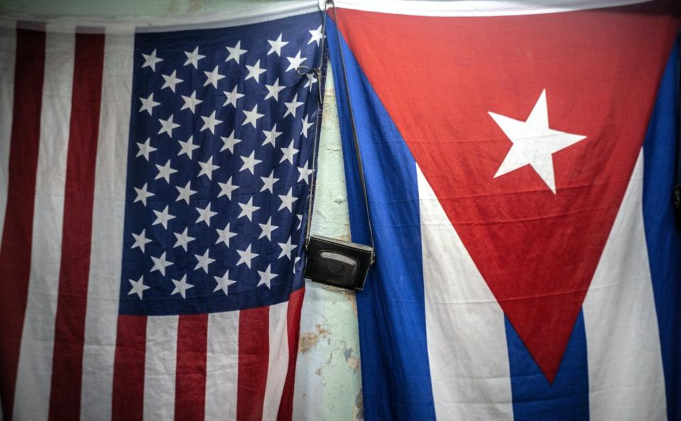 """<span class=""""caption"""">American and Cuban flags hang from a wall with an old camera hung in between in Havana, Cuba, on Jan. 11, 2021.</span> <span class=""""attribution""""><span class=""""source"""">(AP Photo/Ramon Espinosa)</span></span>"""