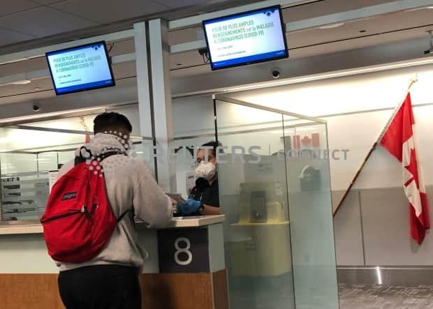 A Canada Border Services Agency (CBSA) officer wears a protective face mask as she checks the passports of passengers arriving at Toronto Pearson International Airport on March 15, 2020.