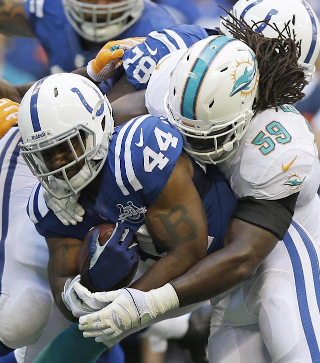 Indianapolis Colts' Ahmad Bradshaw (44) is tackled by Miami Dolphins' Dannell Ellerbe (59) during the first half an NFL football game Sunday, Sept. 15, 2013, in Indianapolis. (AP Photo/Michael Conroy)
