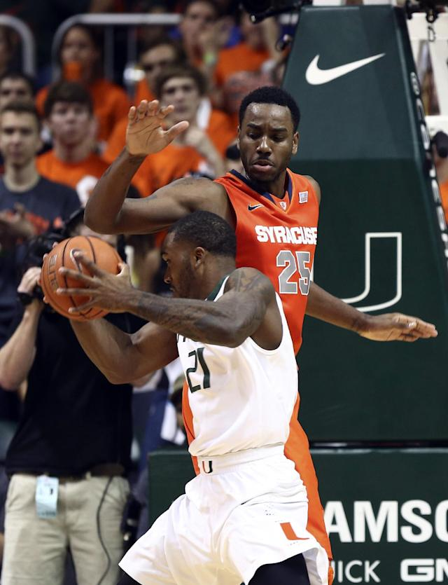 Miami's Erik Swoope (21) squeezes under Syracuse's Rakeem Christmas (25) for a shot on goal during the first half of an NCAA college basketball game in Coral Gables, Fla., Saturday, Jan. 25, 2014. (AP Photo/J Pat Carter)