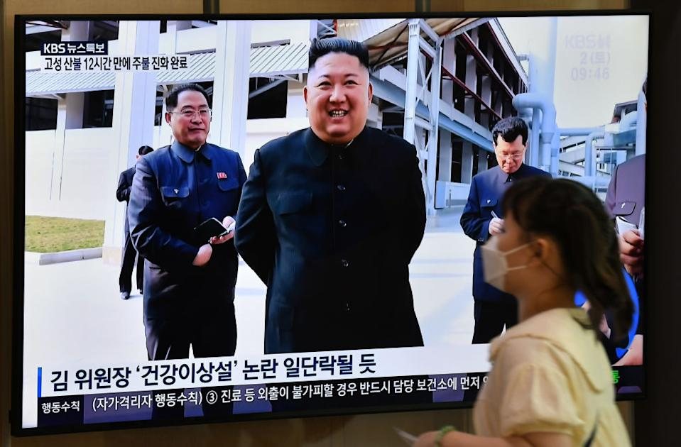 A woman walks past a television news screen showing a picture of North Korean leader Kim Jong Un attending a ceremony on May 2. Source: Getty