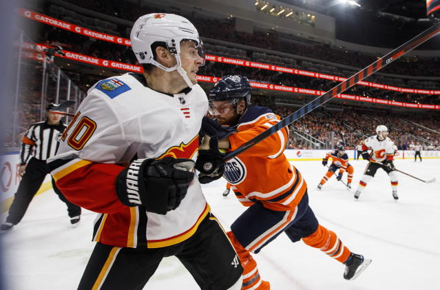 Calgary Flames' Derek Ryan (10) is checked by Edmonton Oilers' Adam Larsson (6) during the third period of an NHL hockey game in Edmonton, Alberta, Saturday, Jan. 19, 2019. (Jason Franson/The Canadian Press via AP)