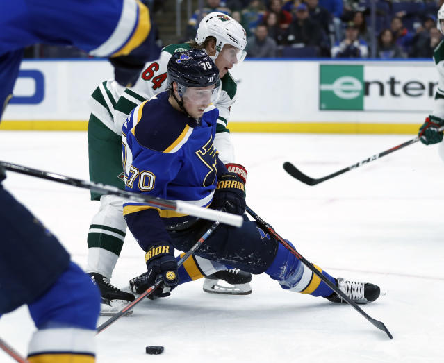 St. Louis Blues' Oskar Sundqvist (70), of Sweden, slips as he brings the puck downice with Minnesota Wild's Mikael Granlund (64), of Finland, during the second period of an NHL hockey game Sunday, Nov. 11, 2018, in St. Louis. (AP Photo/Jeff Roberson)