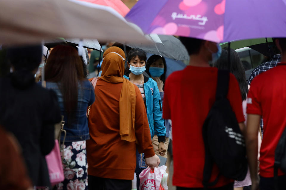 People wearing protective masks cross a street in the rain in Singapore.
