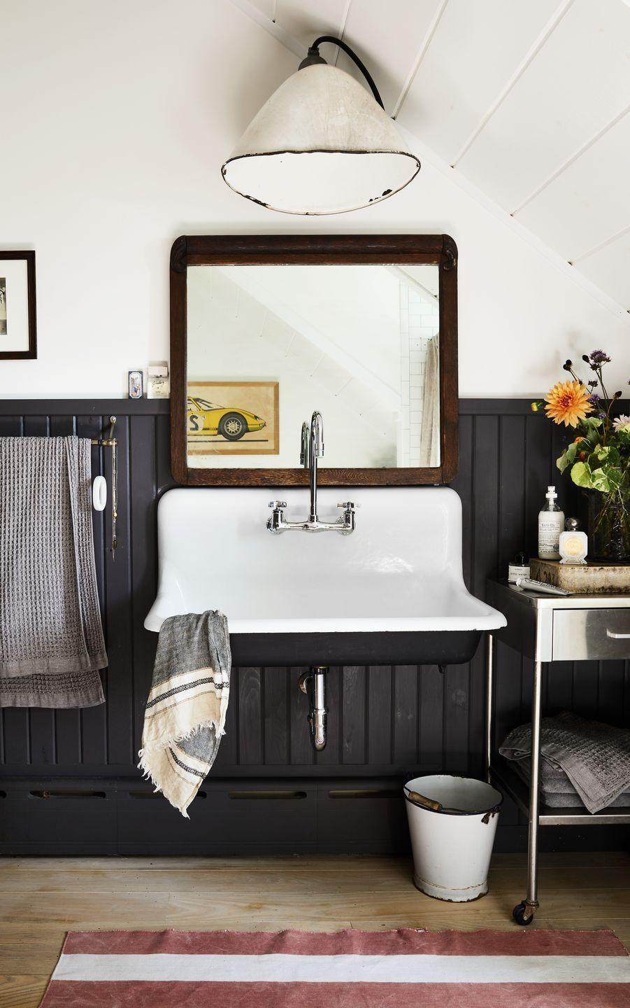 """<p>This curated bathroom strikes the perfect balance between masculine and feminine. A vintage wall sink vanity and a stainless steel rolling table look thoughtfully placed against a black beadboard wall. For a similar look, try <a href=""""https://www.behr.com/consumer/colors/paint/color/N490-7"""" rel=""""nofollow noopener"""" target=""""_blank"""" data-ylk=""""slk:Ink Black by Behr"""" class=""""link rapid-noclick-resp"""">Ink Black by Behr</a>.</p>"""