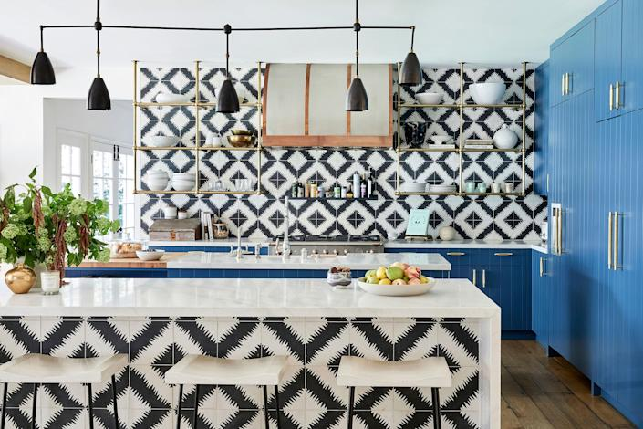 The kitchen features funky black-and-white tiles and a bold pop of blue. (Jenna Peffley / Architectural Digest)