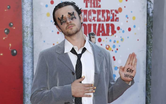 Canadian-American singer and songwriter Grandson shows the words 'Get Vaxxed' written on his hand as he poses on the red carpet prior to the world premiere of DC Film's 'The Suicide Squad' at the Regency Village Theatre in Los Angeles, California - Caroline Brehman/Shutterstock
