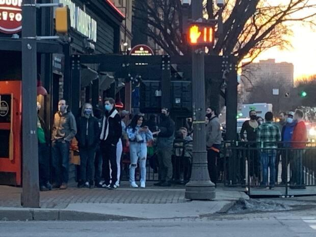 Some patrons lining up to get into a popular bar on Whyte Avenue in March did not follow physical distancing rules.   (Natasha Riebe/CBC - image credit)