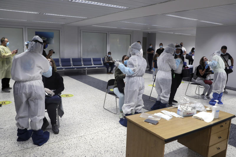 Healthcare workers take swab samples from passengers who arrived at the Rafik Hariri International Airport in Beirut, Lebanon, Wednesday, July 1, 2020. Beirut's airport is partially reopening after a three-month shutdown and Lebanon's cash-strapped government is hoping that thousands of Lebanese expatriates will return for the summer, injecting dollars into the country's sinking economy. (AP Photo/Bilal Hussein)