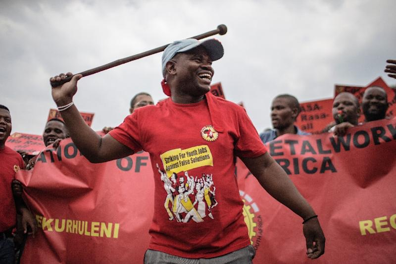 A member of the National Union of Metalworkers of South Africa (NUMSA) waves a baton during an anti-corruption rally in Johannesburg, on October 14, 2015 (AFP Photo/Gianluigi Guercia)