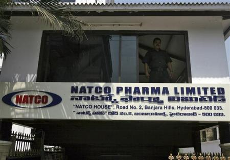 A private security guard looks out from a window of the head office of Natco in the southern Indian city of Hyderabad
