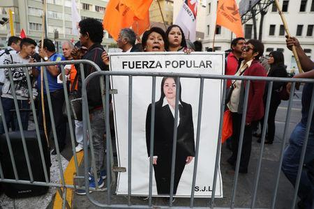 Supporters of opposition leader Keiko Fujimori hold a picture of her, as they wait outside a court where she is attending a hearing, in Lima, Peru October 31, 2018. REUTERS/Mariana Bazo