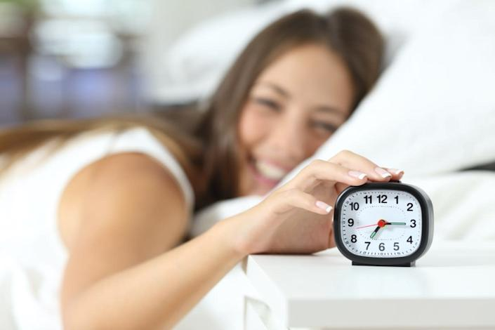 Happy girl waking up in the morning turning off the alarm clock in her bedroom