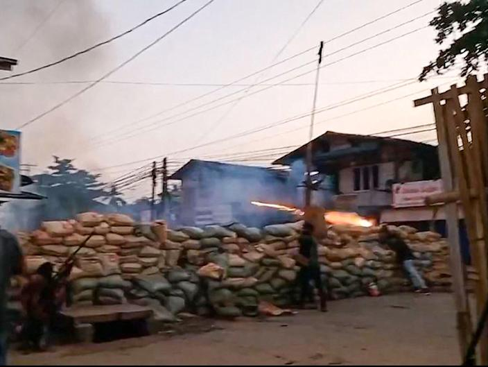 <p>Protesters set off fireworks from behind a barricade during a military crackdown on demonstrations in Bago</p> (AFPTV/AFP via Getty)