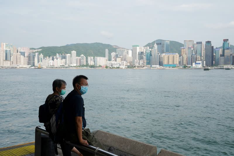 FILE PHOTO: People look on at the Tsim Sha Tsui ferry pier in Hong Kong