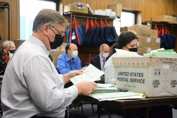 PHOTO: Election Bureau Director Albert L. Gricoski, left, opens provisional ballots next to election bureau staff Christine Marmas, right, while poll watchers observe from behind at the Schuylkill County Election Bureau in Pottsville, Pa., Nov. 10, 2020. (Lindsey Shuey/The Republican-Herald via AP)