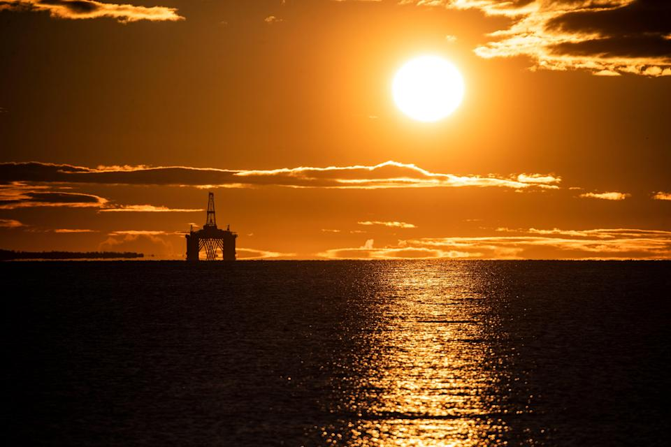 The sun rises behind a redundant oil platform n the Firth of Forth (PA Archive)