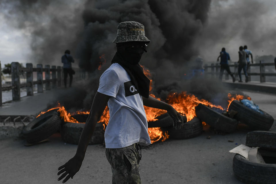 A protester demanding justice for the assassinated President Jovenel Moise stands near a burning barricade in Cap-Haitien, Haiti, Thursday, July 22, 2021. Demonstrations after a memorial service for Moise turned violent on Thursday afternoon with protesters shooting into the air, throwing rocks and overturning heavy concrete barricades next to the seashore as businesses closed and people took cover. (AP Photo/Matias Delacroix)