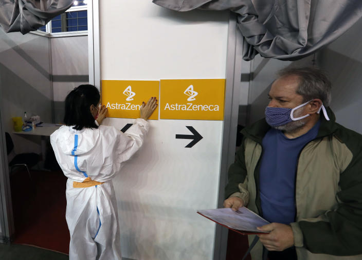 In this photo taken Sunday, March 21, 2021, a medical worker wearing protective gear sets up boards with the names of the vaccines at a vaccination center in Belgrade, Serbia. The Serbian police brought for questioning on Thursday a known Serbian doctor and some other vocal anti-vaccination activists, saying they are jeopardizing the Balkan country's so-far successful coronavirus inoculation drive. (AP Photo/Darko Vojinovic)