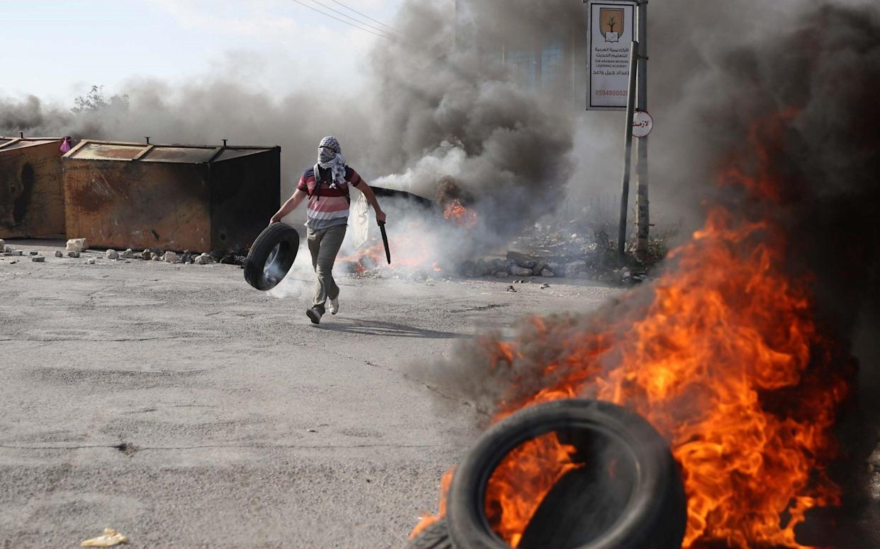 Palestinian protesters burn tires on the blockaded Gaza Strip near Beit El checkpoint in Ramallah, West Bank. The two main militant groups are disagreeing over how to deal with Israel - Anadolu