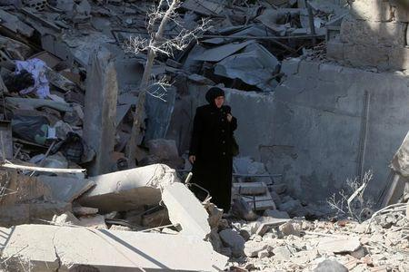 A woman inspects a damaged building after an airstrike on Aleppo's rebel held Saif al-Dawla district