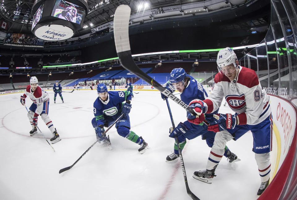 Vancouver Canucks' Quinn Hughes (43) and Montreal Canadiens' Corey Perry (94) vie for the puck as Canadiens' Jesperi Kotkaniemi (15) and Canucks' Jay Beagle (83) watch during the first period of an NHL hockey game Saturday, Jan. 23, 2021, Vancouver, British Columbia. (Darryl Dyck/The Canadian Press via AP)