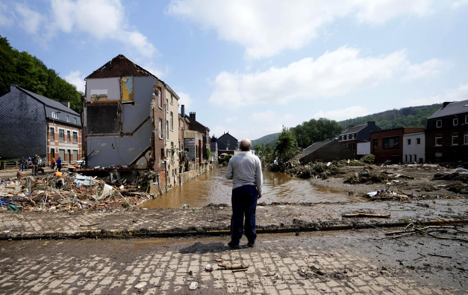 In this Saturday, July 17, 2021 file photo, a man stands on a bridge and surveys the damage after flooding in Pepinster, Belgium.The Walloon government, has announced a 2 billion euro plan for reconstruction in the storm hit region but money alone won't cover for all the losses suffered by the area. For many residents the trauma they experienced will forever stay in their minds. (AP Photo/Virginia Mayo, File)